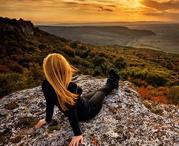 Chica sentada viendo unas montañas