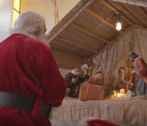 Papa Noel Rezando frente al Pesebre